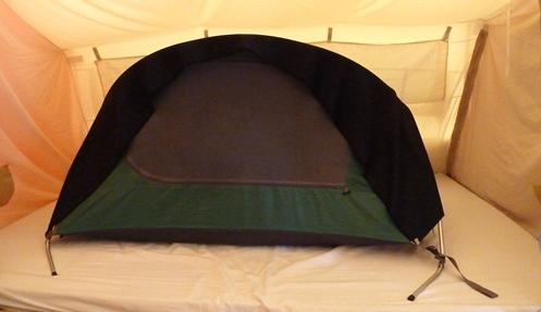 Een donkere deken over het tentje voor de warmte en tegen het licht in de vouwwagen