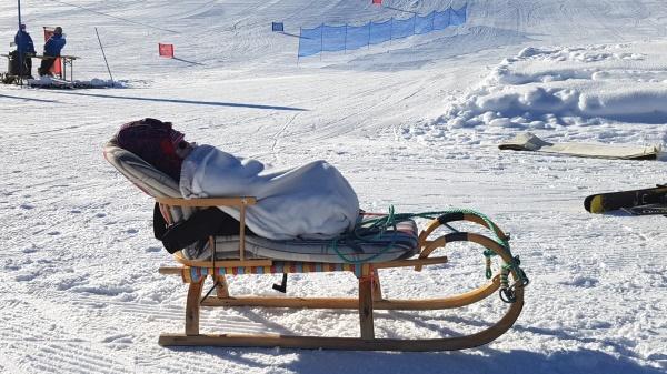 Baby op houten slee wintersport